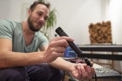 Μουσικός στο στούντιο εγχώριας μουσικής που συνδέει το μικρόφωνο μέσα και που εξετάζει στοκ φωτογραφίες