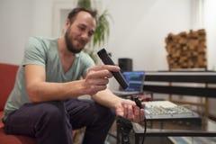 Μουσικός στο στούντιο εγχώριας μουσικής που συνδέει το μικρόφωνο μέσα και που εξετάζει στοκ φωτογραφία με δικαίωμα ελεύθερης χρήσης