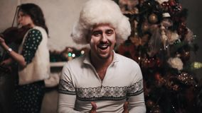 Μουσικός στο τραγούδι καπέλων γουνών με τη συνεδρίαση κουαρτέτων σειράς κοντά στο χριστουγεννιάτικο δέντρο φιλμ μικρού μήκους