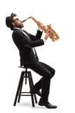 Μουσικός της Jazz που κάθεται σε μια καρέκλα που παίζει ένα saxophone Στοκ φωτογραφία με δικαίωμα ελεύθερης χρήσης