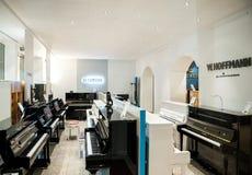 Μουσικό κατάστημα οργάνων με το πιάνο πολυτέλειας και το μεγάλο πιάνο από το Πε Στοκ Εικόνα
