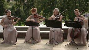 μουσικό κουαρτέτο παιχνιδιού οργάνων παιδιών Τρεις παίζοντας μουσική βιολιστών και βιολοντσελιστών απόμακρη πιθανότητα φιλμ μικρού μήκους