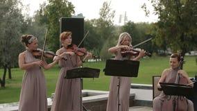 μουσικό κουαρτέτο παιχνιδιού οργάνων παιδιών Τρεις παίζοντας μουσική βιολιστών και βιολοντσελιστών Μέσος πυροβολισμός απόθεμα βίντεο