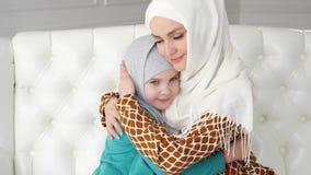Μουσουλμάνος mom και λίγη κόρη στα hijabs αγκαλιάζουν τη συνεδρίαση στον καναπέ φιλμ μικρού μήκους
