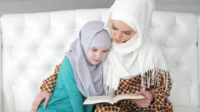 Μουσουλμάνος mom στο hijab της διαβάζει λίγη κόρη μια συνεδρίαση βιβλίων στον καναπέ απόθεμα βίντεο