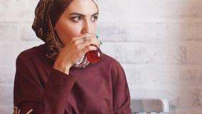 Μουσουλμανικά έγγραφα εργασίας επιχειρησιακών γυναικών στον καφέ φιλμ μικρού μήκους