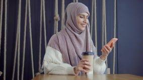 Μουσουλμανική γυναίκα με ένα smartphone φιλμ μικρού μήκους