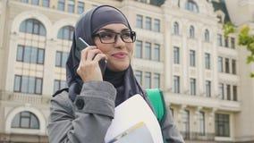 Μουσουλμανική γυναίκα που μιλά στο τηλέφωνο, που περιμένει κοντά στο κολλέγιο τις κατηγορίες, μελέτη στο εξωτερικό απόθεμα βίντεο