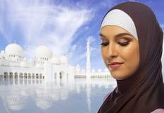 Μουσουλμανική γυναίκα στο άσπρο υπόβαθρο μουσουλμανικών τεμενών στοκ φωτογραφία