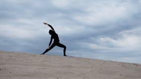 Μουσουλμανική γυναίκα στο hijab που ασκεί την υγιή άσκηση γιόγκας τρόπου ζωής στην έρημο στο ηλιοβασίλεμα Στοκ Φωτογραφίες