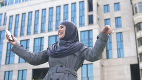 Μουσουλμανικό κορίτσι που παρουσιάζει ναι χειρονομία μετά από τις διαβασμένες καλές ειδήσεις στο τηλέφωνο, επιτυχής σταδιοδρομία απόθεμα βίντεο