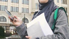 Μουσουλμανικό κορίτσι που χρησιμοποιεί το τηλέφωνο, που περιμένει τους φίλους κοντά στο κολλέγιο, εκπαίδευση στην Ευρώπη φιλμ μικρού μήκους