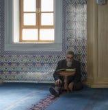 Μουσουλμάνοι βρίσκουν την ειρήνη με την ανάγνωση του Quran στο μουσουλμανικό τέμενος Στοκ Φωτογραφία