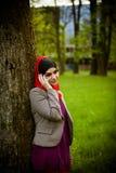 Μουσουλμανική γυναίκα που μιλά στο τηλέφωνο και που χρησιμοποιεί την τεχνολογία Η μουσουλμανική γυναίκα χρησιμοποιεί το έξυπνο τη Στοκ Φωτογραφία