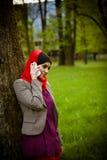 Μουσουλμανική γυναίκα που μιλά στο τηλέφωνο και που χρησιμοποιεί την τεχνολογία Η μουσουλμανική γυναίκα χρησιμοποιεί το έξυπνο τη Στοκ Φωτογραφίες