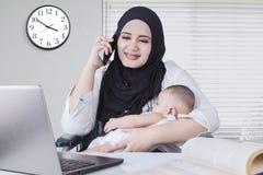 Μουσουλμανική γυναίκα που περιποιείται το μωρό της εργαζόμενη Στοκ Εικόνες