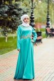 Μουσουλμανική γυναίκα στο ασιατικό φόρεμα και λευκό μαντίλι για το κεφάλι στο κεφάλι της στο πάρκο Στοκ Φωτογραφία
