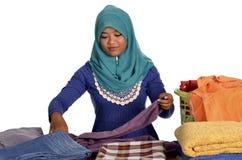 Μουσουλμανική κυρία που διπλώνει τα ενδύματα στοκ φωτογραφίες