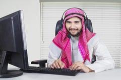 Μουσουλμανικός χειριστής που εργάζεται με τον υπολογιστή και το ακουστικό Στοκ Εικόνες