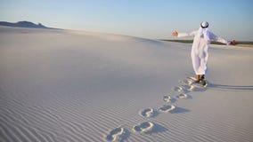 Μουσουλμανικό αραβικό Sheikh ατόμων στην καλή διάθεση περπατά την άσπρη αμμώδη έρημο και απολαμβάνει τη σαφή ημέρα σε υπαίθριο απόθεμα βίντεο