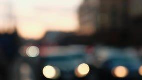 Μουτζουρωμένα φω'τα αυτοκινήτων Defocused που περνούν από στην κυκλοφοριακή συμφόρηση, ηλιοβασίλεμα στο υπόβαθρο φιλμ μικρού μήκους