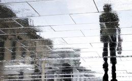 Μουτζουρωμένες σκιαγραφίες αντανάκλασης των ανθρώπων που περπατούν μια βροχερή ημέρα Στοκ Φωτογραφία