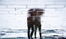 Μουτζουρωμένες σκιαγραφίες σκιών αντανάκλασης ενός ζεύγους κάτω από την ομπρέλα Στοκ Φωτογραφία
