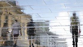 Μουτζουρωμένες σκιαγραφίες σκιών αντανάκλασης των ανθρώπων που περπατούν σε μια βροχή Στοκ Εικόνες