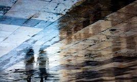 Μουτζουρωμένη σκιά αντανάκλασης μιας γυναίκας στο υγρό πεζοδρόμιο Στοκ Φωτογραφία