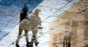 Μουτζουρωμένη σκιά αντανάκλασης δύο ανθρώπων και ενός σκυλιού στο υγρό πεζοδρόμιο Στοκ φωτογραφία με δικαίωμα ελεύθερης χρήσης