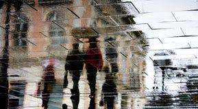 Μουτζουρωμένη σκιαγραφία αντανάκλασης των ανθρώπων που περπατούν στη βροχή Στοκ Εικόνα