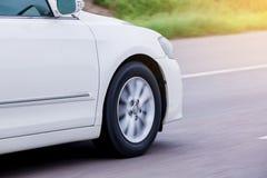 Μουτζουρωμένος της άσπρης ρόδας αυτοκινήτων που περιστρέφεται με να τρέξει με υψηλή ταχύτητα στοκ εικόνες