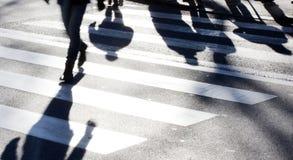 Μουτζουρωμένο ζέβες πέρασμα με τους πεζούς που κάνουν τις μακριές σκιές Στοκ Εικόνες