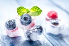 Μούρα που παγώνουν στους κύβους πάγου με τη μέντα στο ξύλινο επιτραπέζιο υπόβαθρο Στοκ Εικόνες