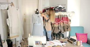 Μοδίστρα που χρησιμοποιεί το μανεκέν για το ράψιμο του όμορφου φορέματος απόθεμα βίντεο