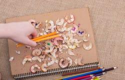 Μολύβια χρώματος εκμετάλλευσης χεριών πέρα από ένα σημειωματάριο Στοκ εικόνα με δικαίωμα ελεύθερης χρήσης