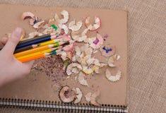 Μολύβια χρώματος εκμετάλλευσης χεριών πέρα από ένα σημειωματάριο Στοκ εικόνες με δικαίωμα ελεύθερης χρήσης
