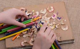 Μολύβια χρώματος εκμετάλλευσης χεριών πέρα από ένα σημειωματάριο Στοκ Εικόνες