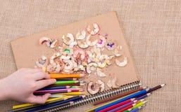 Μολύβια χρώματος εκμετάλλευσης χεριών πέρα από ένα σημειωματάριο Στοκ φωτογραφία με δικαίωμα ελεύθερης χρήσης