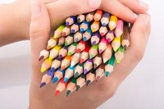 Μολύβια χρώματος εκμετάλλευσης χεριών Στοκ Φωτογραφίες