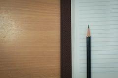 Μολύβι και βιβλίο στον ξύλινο πίνακα Τοπ όψη Στοκ φωτογραφίες με δικαίωμα ελεύθερης χρήσης