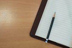 Μολύβι και βιβλίο στον ξύλινο πίνακα Τοπ όψη Στοκ Εικόνα