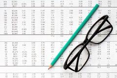 Μολύβι και γυαλιά στο οικονομικό διάγραμμα Στοκ Εικόνα