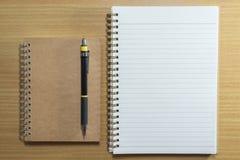 Μολύβι, στυλός και σημειωματάριο στον ξύλινο πίνακα Τοπ όψη Στοκ φωτογραφίες με δικαίωμα ελεύθερης χρήσης