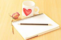 Μολύβι, φλιτζάνι του καφέ, τριαντάφυλλα και βιβλίο στον ξύλινο πίνακα στοκ εικόνες