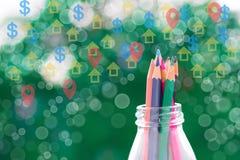 Μολύβι χρώματος στο μπουκάλι με το διάνυσμα νομίσματος σπιτιών και δολαρίων σε ένα θολωμένο υπόβαθρο δέντρων στη φύση χρησιμοποίη Στοκ φωτογραφία με δικαίωμα ελεύθερης χρήσης