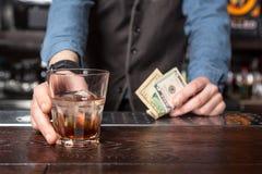 Μπάρμαν με το γυαλί ουίσκυ και χρήματα στα χέρια του στοκ φωτογραφίες με δικαίωμα ελεύθερης χρήσης