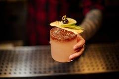 Μπάρμαν που κρατά ένα γυαλί κοκτέιλ γεμισμένο με το νόστιμο γλυκό οινοπνευματώδες ποτό με τις φέτες πάγου και φρούτων στοκ εικόνες με δικαίωμα ελεύθερης χρήσης