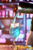 Μπάρμαν που χύνει ένα κοκτέιλ σε μια λέσχη γυαλιού τη νύχτα Στοκ Φωτογραφίες