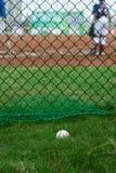 Μπέιζ-μπώλ έξω από έναν τομέα μπέιζ-μπώλ με το κτύπημα και catcher στο υπόβαθρο Στοκ Εικόνες